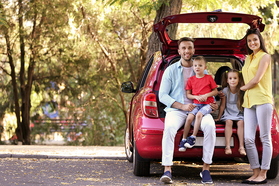 Personalized Insurance - Family with Kids Sitting in Car Trunk Parked Along the Street of a Suburban Neighborhood